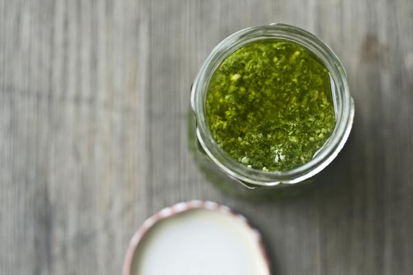 Ein Glas giftgrünes Bärlauch-Sesam-Pesto steht auf einem Holztisch