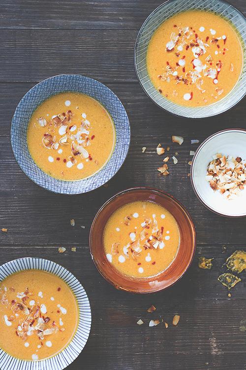 Scharfe Kürbis-Erdnuss-Suppe auf fünf Tellern, garniert mit Kokoschips |Rezepte mit Hokkaido-Kürbis